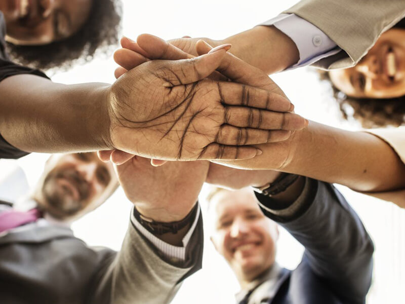 Business men and women with hands together in a circle