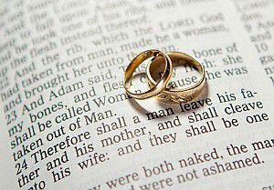 Two Gold Wedding Bans Stacked on Page of Bible